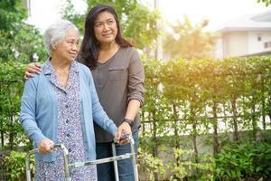 Hilfe und Pflege asiatische Senioren oder ältere alte Damen verwenden einen Walker mit starker Gesundheit, während sie im Park in einem glücklichen, frischen Urlaub spazieren gehen. foto