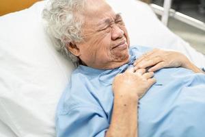Asiatische Senioren oder ältere Frauenpatienten fühlen Schmerzen in der Brust und im Herzen auf dem Bett in der Krankenstation foto