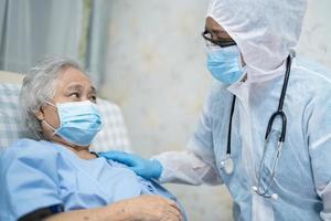 Arzt, der ein Stethoskop verwendet, um asiatische Senioren oder ältere Frauen mit einer Gesichtsmaske im Krankenhaus zu überprüfen, um die Infektion mit dem Covid-19-Coronavirus zu schützen. foto