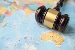 Bangkok, thailand - 1. dezember 2020 - australien - hammer für richteranwalt auf weltkarte. Recht und Gerechtigkeit Gericht Konzept foto