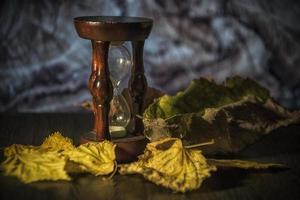 Herbstlaub und eine Sanduhr auf einem Tisch foto