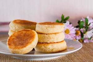 Käsekuchen auf einem Teller auf braunem Hintergrund. Teller mit Hüttenkäse zum Frühstück. foto