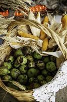 Mais und Kürbisse in einem traditionellen Korb foto