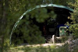 Ein alter Traktor versteckt sich unter dem Schuppen auf dem Land, Frankreich foto