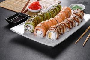 frische leckere Sushi-Rollen in Form eines Drachen mit Ingwer und Wasabi foto