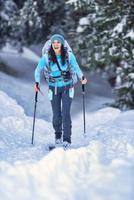 Schönes junges Mädchen, das Skitouren im Wald praktiziert foto