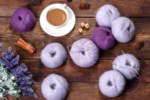 Gewirr von Wollfäden und Speichen mit einer Tasse Kaffee und Zucker auf einem hölzernen Hintergrund foto