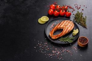 frisch zubereitetes leckeres Lachssteak mit Gewürzen und Kräutern vom Grill gebacken foto