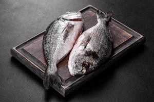 roher Dorado-Fisch mit Gewürzen, die auf Schneidebrett kochen. frischer Fisch Dorado foto