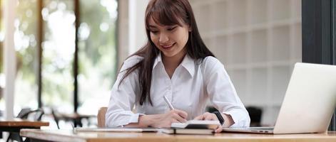 Porträt einer hübschen jungen Frau, die am Tisch sitzt foto