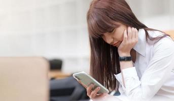 junge Frau in Weiß sitzt mit deinem Smartphone foto