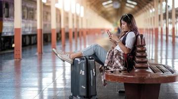 junge Frau, die ihr Smartphone benutzt, während sie auf den Zug wartet foto