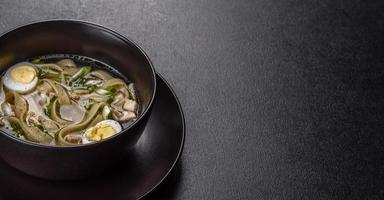 frische leckere heiße Suppe mit Nudeln und Wachtelei in einem schwarzen Teller foto