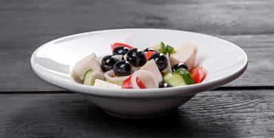 frischer leckerer griechischer Salat mit Tomaten, Gurken, Zwiebeln und Oliven mit Olivenöl foto