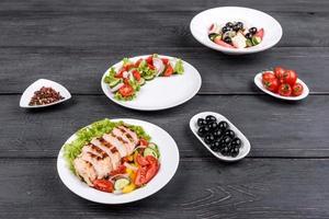 drei frische leckere Salate mit Hühnchen, Tomaten, Gurken, Zwiebeln und Gemüse mit Olivenöl foto