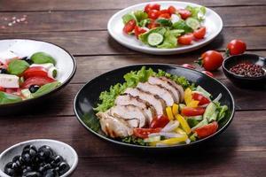 frischer leckerer Salat mit Hühnchen, Tomaten, Gurken, Zwiebeln und Gemüse mit Olivenöl foto