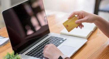 Frau, die Computer benutzt und Kreditkarte für Online-Shopping hält foto