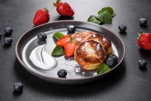 leckere gebackene Pfannkuchen mit Beeren und Minze mit Puderzucker und Topping auf einem grauen Teller foto