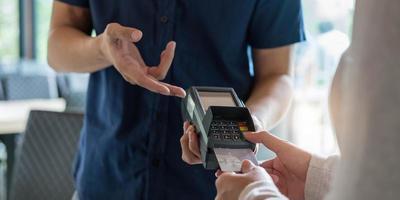 Hand des Kunden, der mit Kreditkarte bezahlt foto