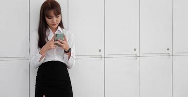 Mädchen steht und benutzt Handy foto