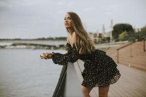 junge brünette Frau mit langen Haaren, die am Flussufer steht foto