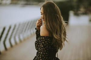 junge brünette Frau mit langen Haaren, die am Flussufer spaziert foto