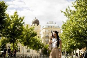 junge Frau, die ein Mobiltelefon beim Gehen auf der Straße benutzt foto