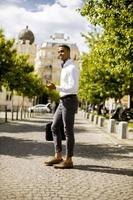junger afroamerikanischer Geschäftsmann, der ein Mobiltelefon auf einer Straße verwendet foto