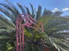 Flamingofigur aus Metall auf dem Hintergrund von Palmblättern foto