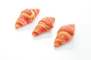 frisches Croissant mit Erdbeermarmelade-Sauce isoliert auf weißem Hintergrund foto