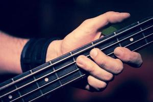 Detail der Hände, die einen E-Bass spielen foto