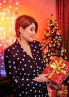 Weihnachtsschießen. schönes Modell mit Neujahrsgeschenken auf dem Hintergrund eines Weihnachtsbaums. foto