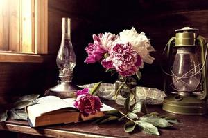 Stillleben mit Vintage-Artikeln und einem Strauß Pfingstrosen auf einem Tisch am Fenster in einem alten Dorfhaus. foto