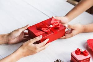 Hand des jungen Menschen, die Geschenkboxdekoration gibt foto