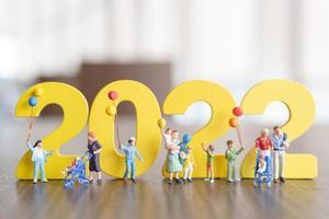 Miniaturmenschen glückliche Familie mit Ballon auf weißer Zahl 2022 foto