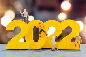 Miniaturmenschen klettern auf Holz mit der Nummer 2022 foto