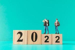 Miniatur-Backpacker und Tourist stehen auf Holzblock Nummer 2022 foto