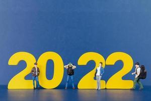 Miniatur-Menschen-Backpacker, der auf Holznummer 2022 steht foto