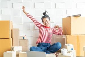 asiatische Geschäftsinhaberin, die zu Hause mit Verpackungsbox am Arbeitsplatz arbeitet - Online-Shopping-KMU-Unternehmer oder freiberufliches Arbeitskonzept foto