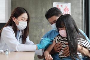 Ärztin mit Gesichtsmaske, die asiatisches Mädchen impft, um Coronavirus Covid-19 in der Kinderklinik im Kinderkrankenhaus mit Vater in der Nähe zu verhindern. Injektionen behandeln Krankheiten, verursachen Schmerzen bei Kindern. foto