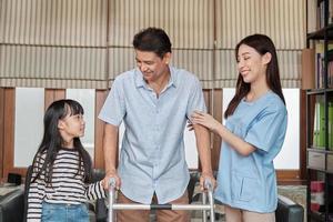 asiatische Physiotherapeutin hilft, trainiert und rehabilitiert einen älteren behinderten Mann in einem Privathaus. Gesundheitsberatung, körperliche Genesung mit einer Enkelin, die daneben unterstützt. foto