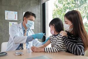 männlicher Arzt impfen asiatisches Mädchen in der Kinderklinik. foto
