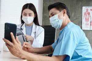 männlicher Patient mit Gesichtsmaske gebeten, ein Selfie mit einer Ärztin zu machen. foto