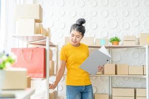 Junge asiatische Frau, die Waren im Lagerregal im Lager überprüft - Online-Verkauf oder Online-Shopping-Konzept foto