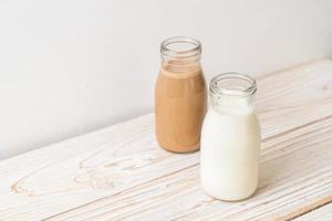 Kaffee und frische Milch in der Flasche auf Holzhintergrund foto