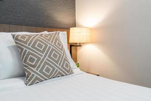 schönes Kissen auf dem Bettdekorationsrauminnenraum foto