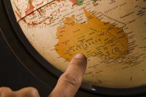 bardejov, slowakei 2018 - der Finger einer Person, der auf das australische Land auf dem Globus zeigt foto