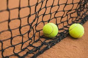 zwei Tennisbälle in der Nähe von schwarzem Netzboden. hochwertiges schönes Fotokonzept foto