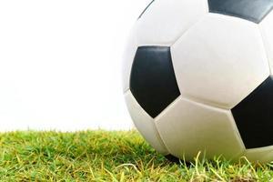 Fußball auf grünem Gras isoliert auf weißem Hintergrund foto