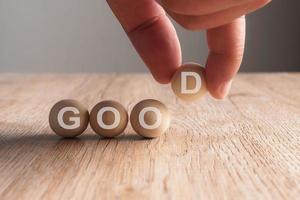 Hand, die ein gutes Wort in Holzkugel geschrieben hat foto
